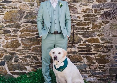 yellow labrador poses for a photo next to a man wearing a mint green suit at his wedding
