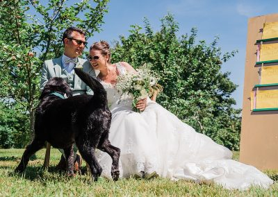 Black labradoodle jumps around next to bride and groom at sunny wedding