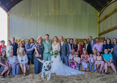 group of people stand together for family photo at wedding with yellow labrador running to camera