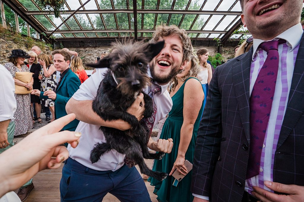 small black dog in arms of man dancing
