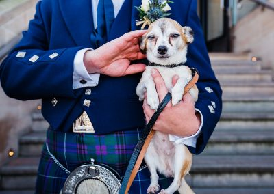 chihuahua held by groom wearing kilt