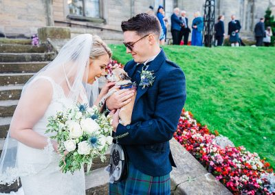 bride nuzzles pet chihuahua held by man in kilt dog friendly wedding