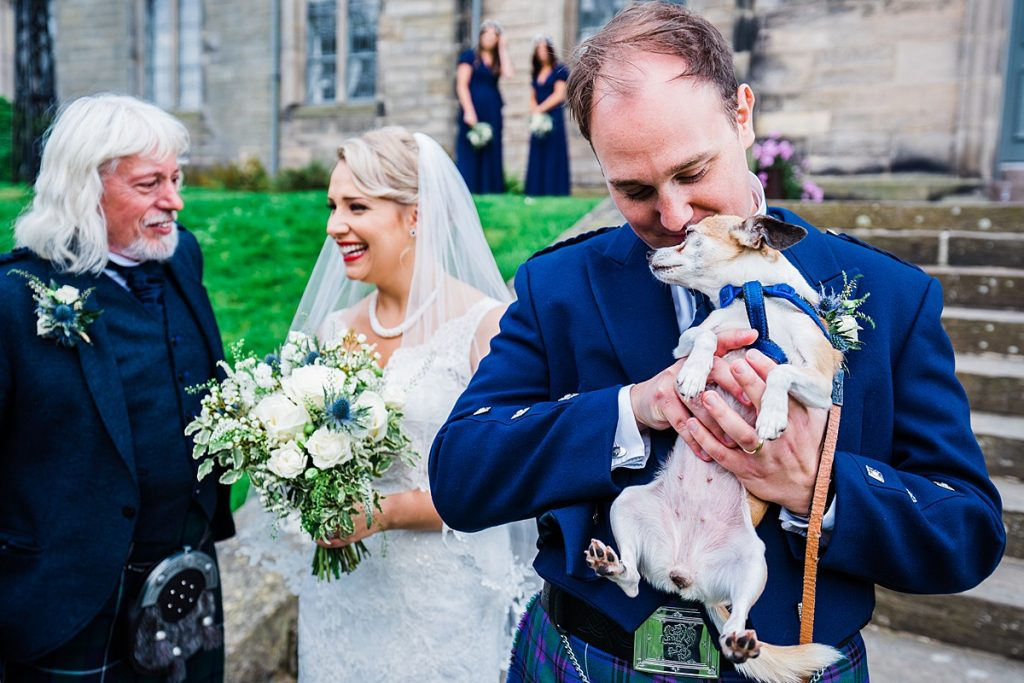 chihuahua held in the arms of a groom wearing a kilt while bride talks to father