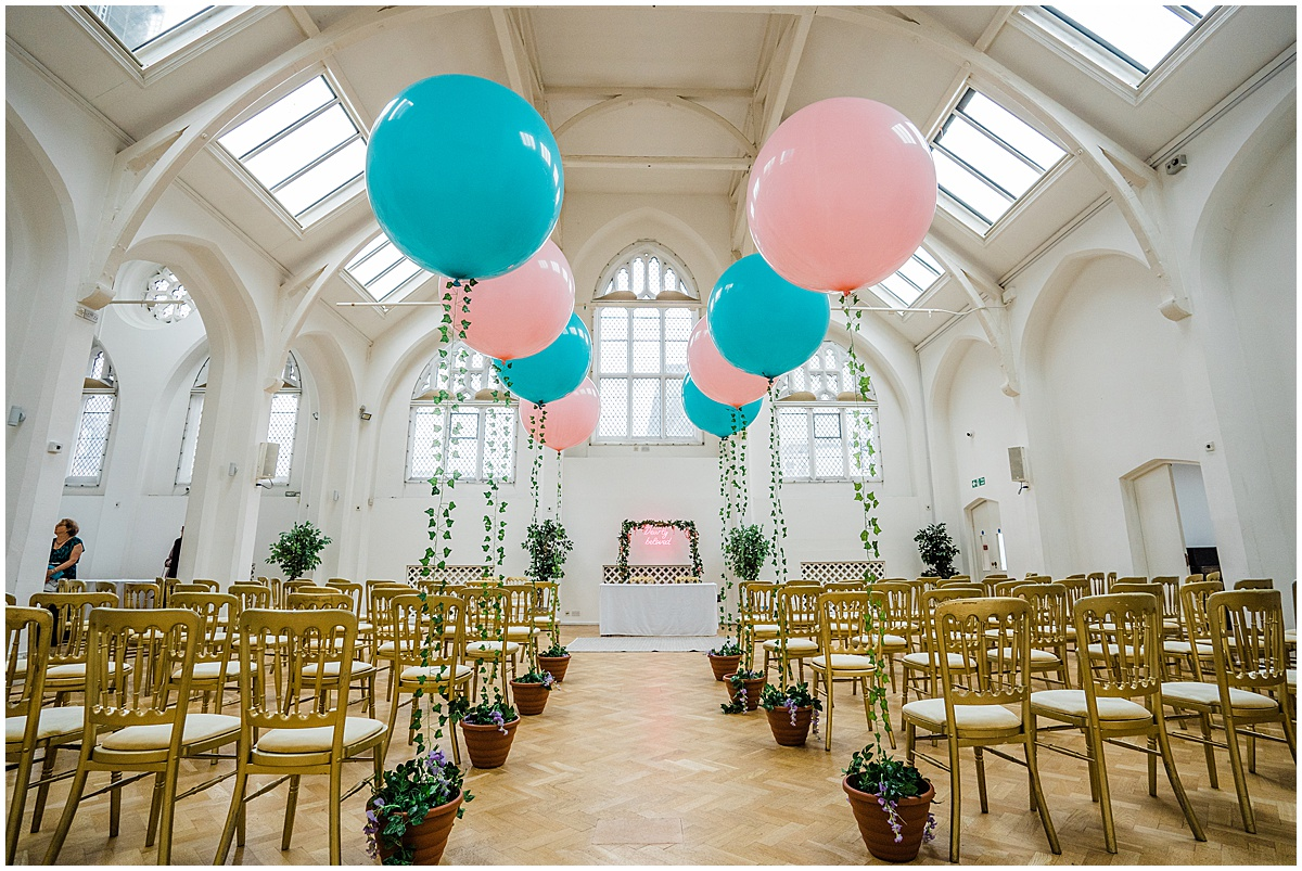 Birmingham wedding venue The Old Library ready for a wedding ceremony with giant blue and pink balloons and gold chairs