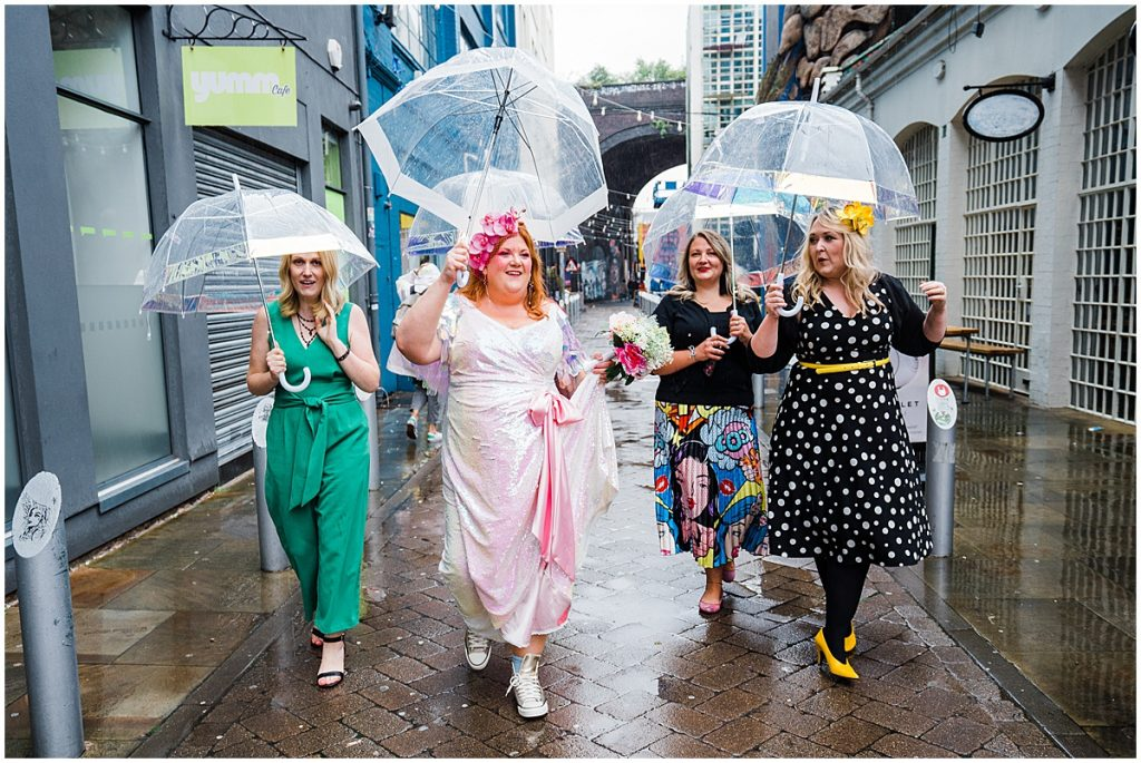 bride wearing pink sequin dress walking down digbeth street with friends all holding umbrellas outside the old library wedding