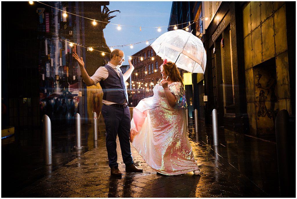 bride and groom dance in the rain outside the old library wedding