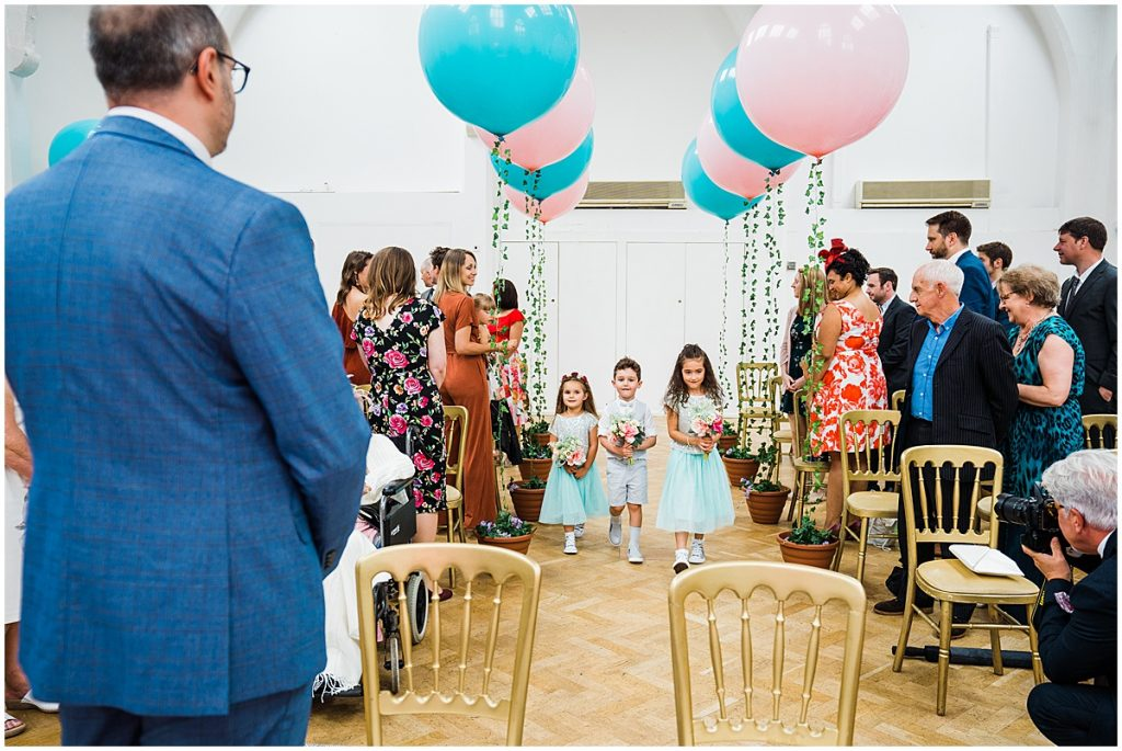 flower girls and flower boy walk down the aisle at the old library wedding