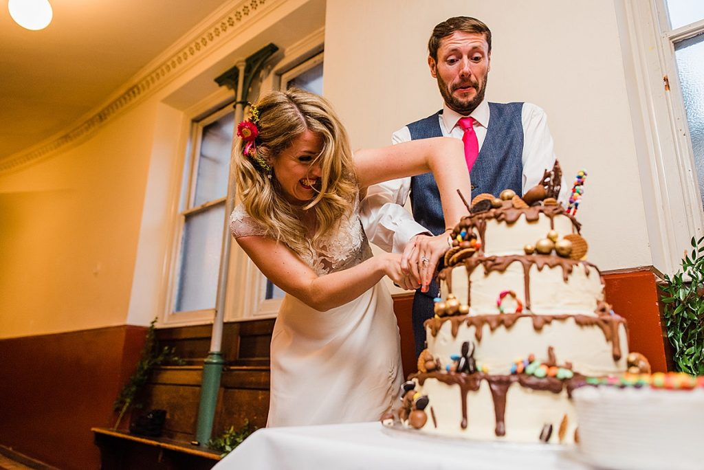bride struggles to cut cake tower with groom at clapton roundhouse wedding