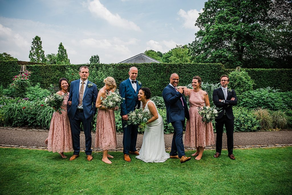 bride and groom stand with bridesmaids and groomsmen laughing for a wedding party group photo