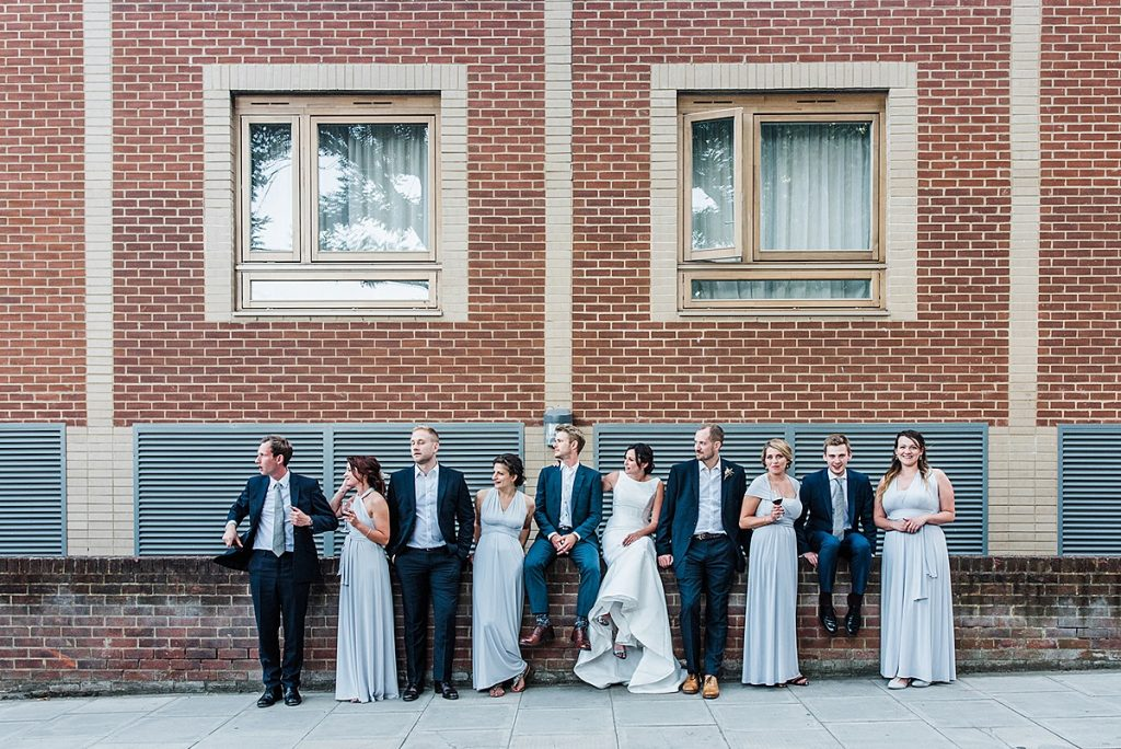 Bridal party pose for a relaxed group photo against a wall in london.