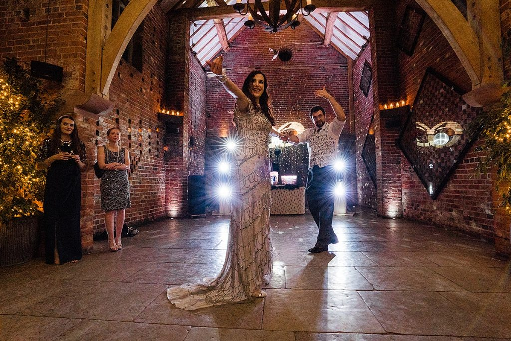 bride and groom welcome guests on to dance floor after first dance at Shustoke Farm Barn Wedding