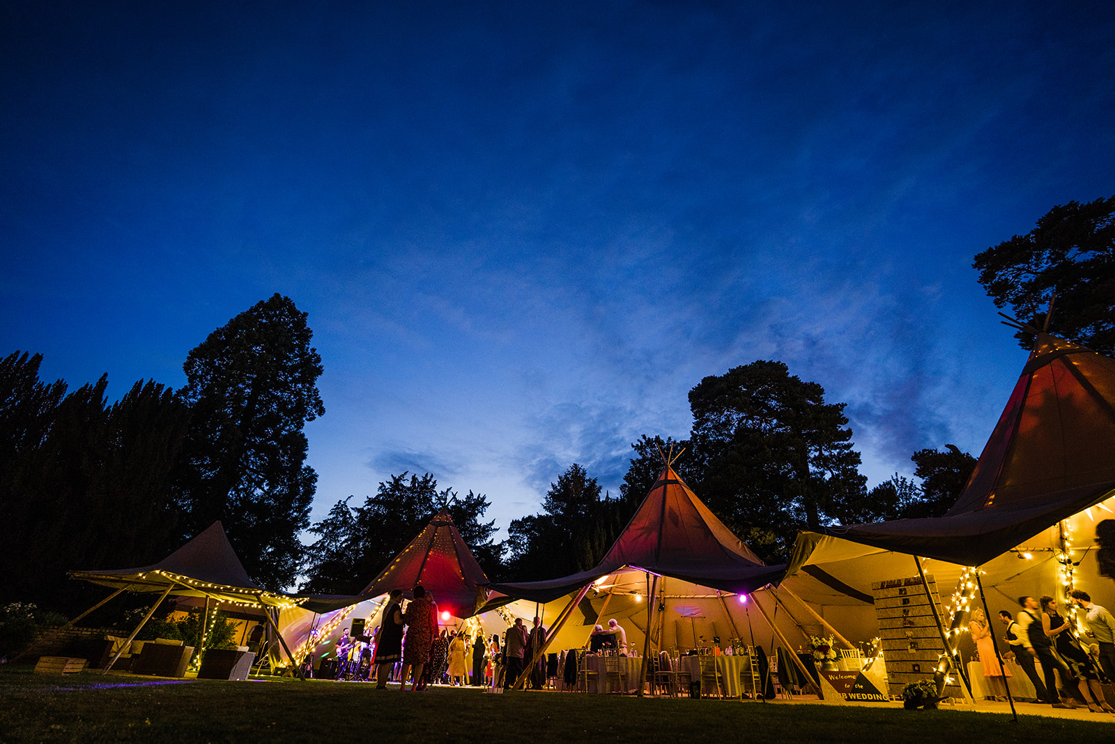 A tipi is full of wedding guests and lit up for a night time photo at relaxed wedding