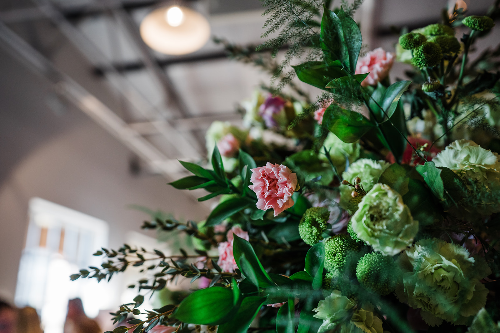 Internal photrograph of alternative wedding venue Birmingham Fazeley Studios showing a green and pink floral arrangement against industrial style ceiling