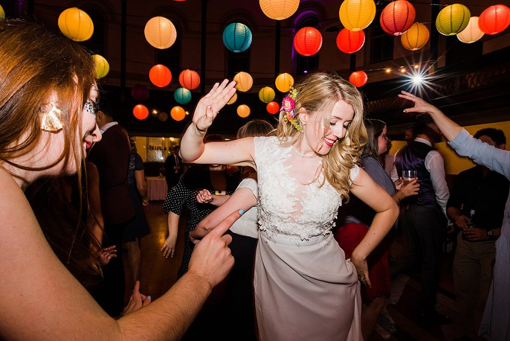 bride dances at fun wedding party on packed dance floor surrounded by colourful paper lanterns