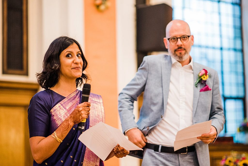 asian bride in purple and pink wedding sari giving a speech as husband looks on