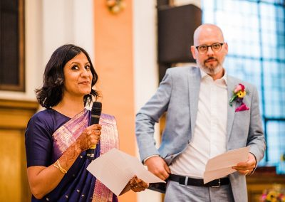 bride smiles at audience during wedding speech as groom looks on nervously