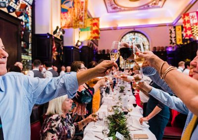 guests clink glasses together during wedding toast