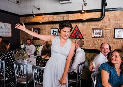 bridesmaid stand sup and welcomes newly wed couple to wedding reception at London pub