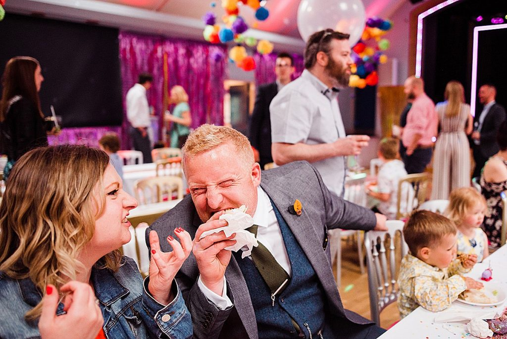 wedding guest bites in to burger at pink themed wedding