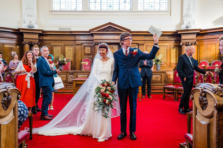 bride and groom walk islington street from registry office wedding