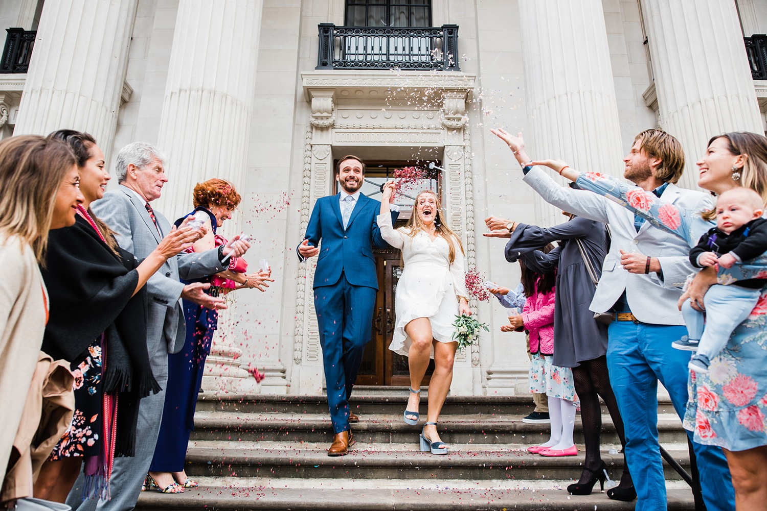 Bride and groom exiting Old Marylebone Town Hall Elopement to confetti