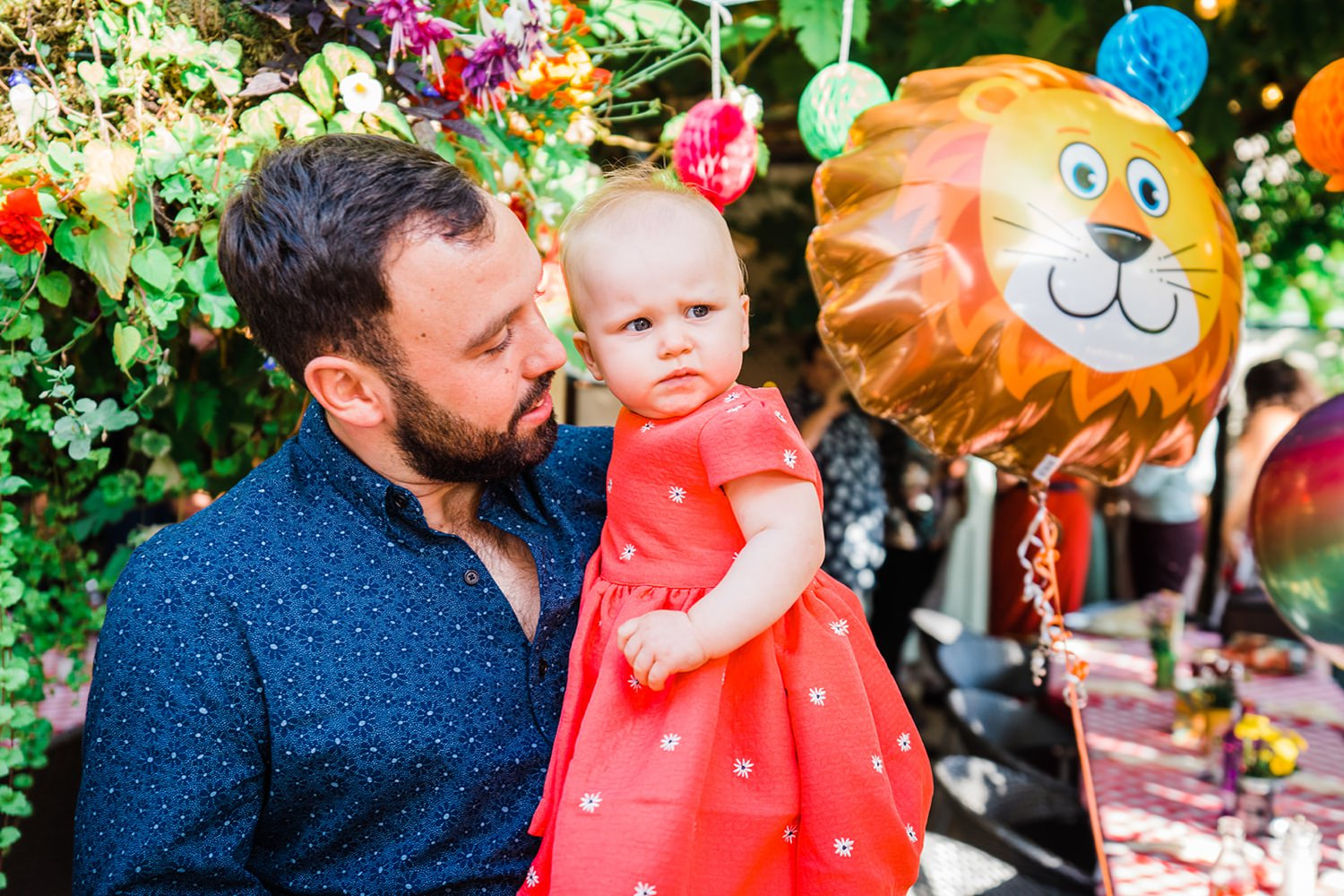 Baby looking at lion balloon small wedding