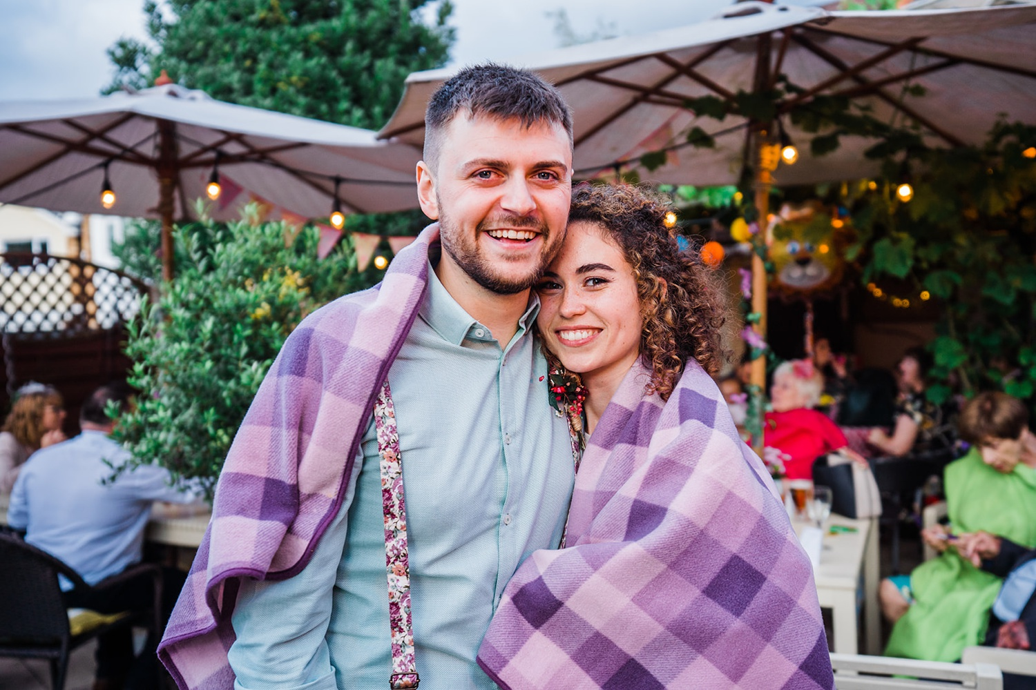 newly wedded couple cuddle together under a blanket at small solihull wedding