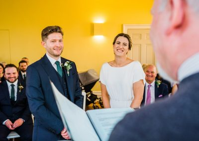 Bride and groom looking at celebrant at Clissold House wedding ceremony
