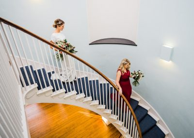 Bride and bridesmaid walking down curved staircase at Clissold House