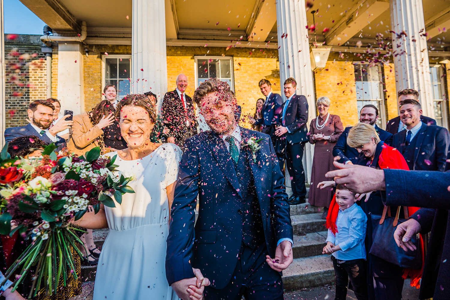 Brde and groom leaving Clissold house to shower of confetti