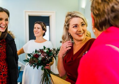 Candid shot of bride and bridesmaid chatting to registrar at Clissold house