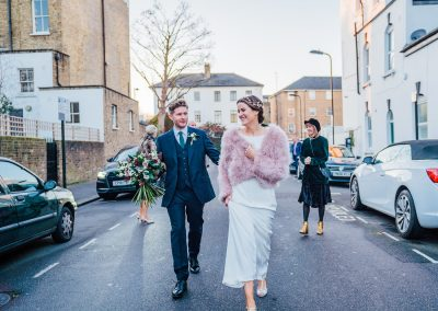 Bride and groom walking down London street holding hands
