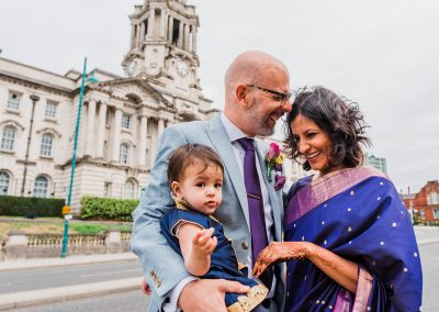 Asian-bride-in-purple-and-pink-bridal-sari-laughing-with-groom-and-daughter-outside-stockport-town-hall