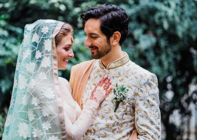 Bride-and-groom-in-indian-wedding-clothes-hug-each-other-and-smile-in-green-garden