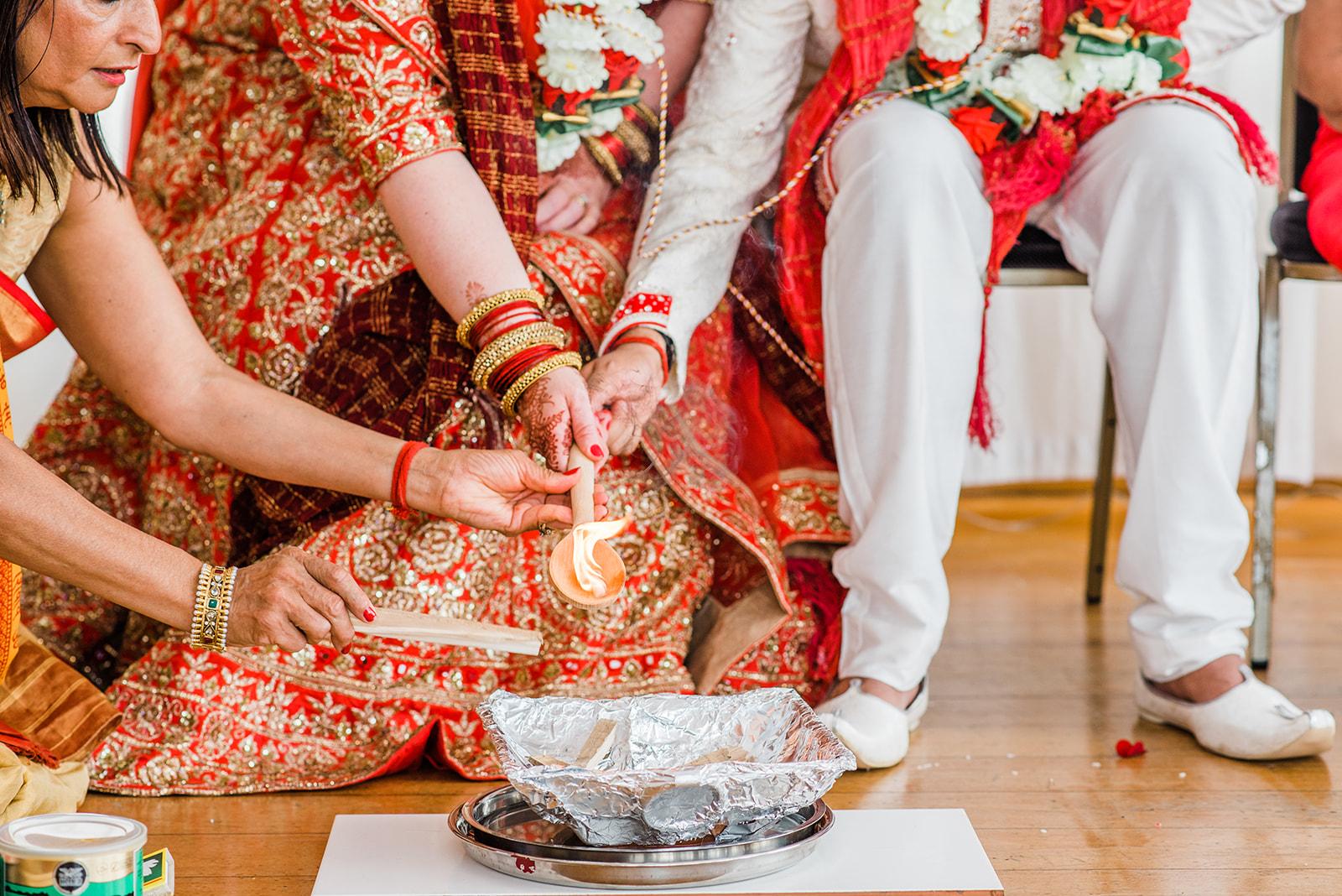 Bride and groom light ceremonial fire at hindu wedding greenwich yacht club