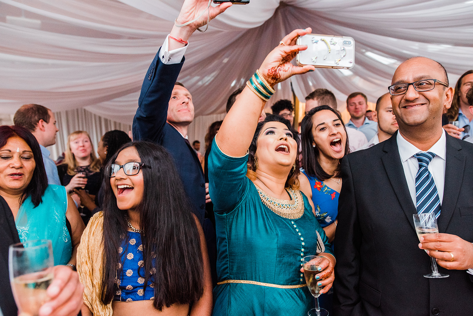 Wedding guests cheer and hold phones up to record wedding speech at cultural fusion wedding at Greenwich Yacht Club
