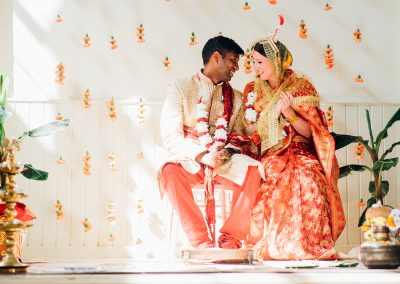 Bride and groom in red indian wedding clothes in pool of light with floral backdrop