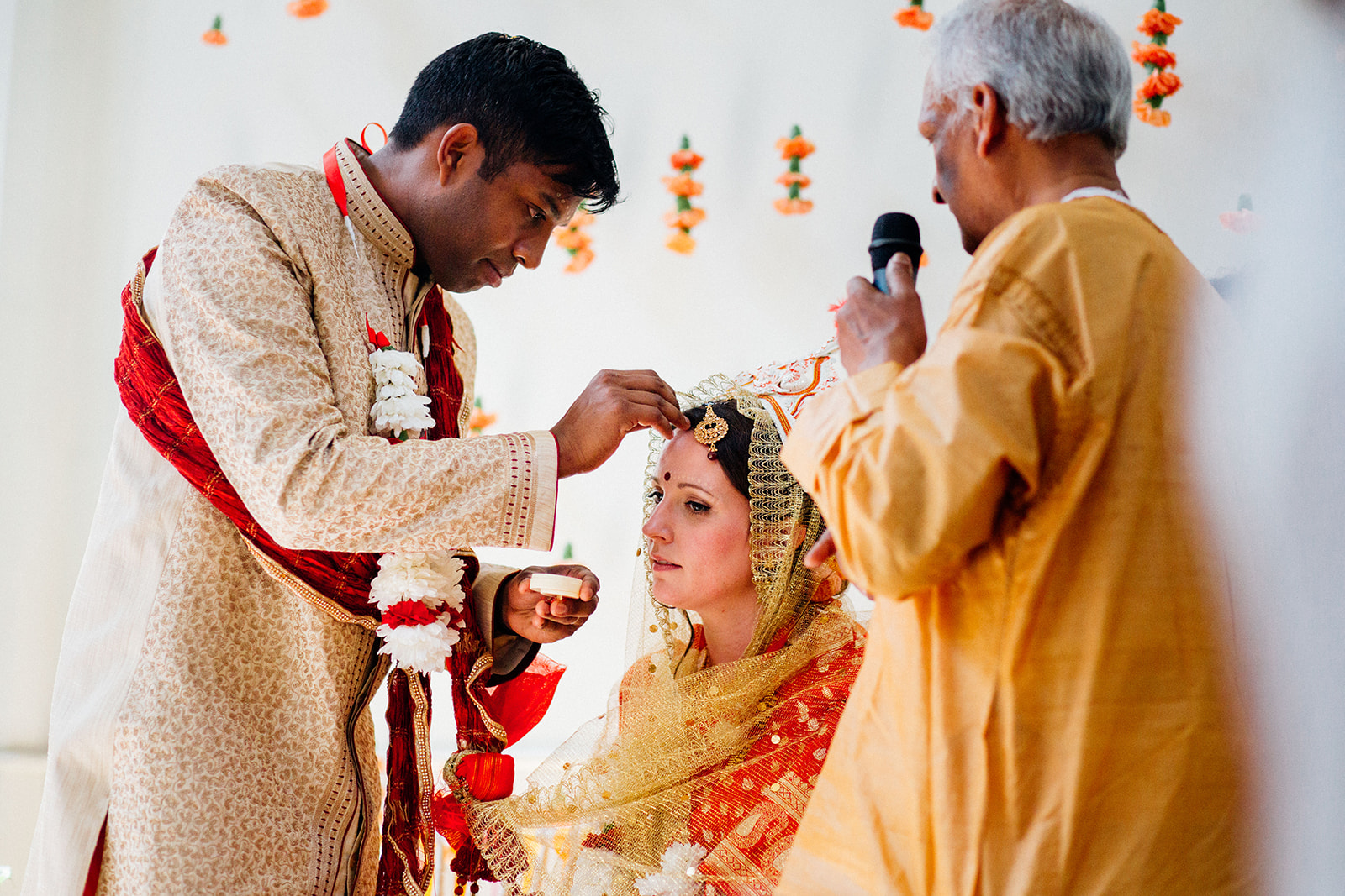 Groom places mark on brides forehead during Hindu wedding ceremony