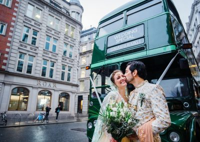 bride-and-groom-embrace-and-laugh-in-front-of-vintage-green-bus-in-central-london
