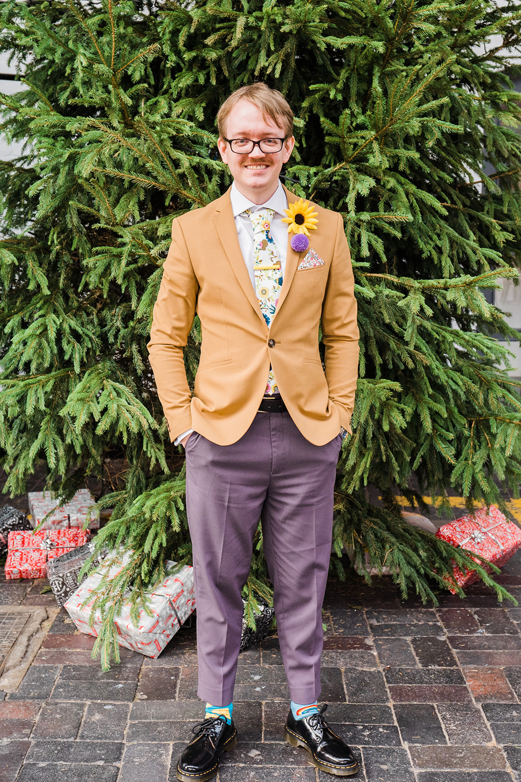 alternative groom wearing mismatched suit with floral pattern tie and sunflower button hole
