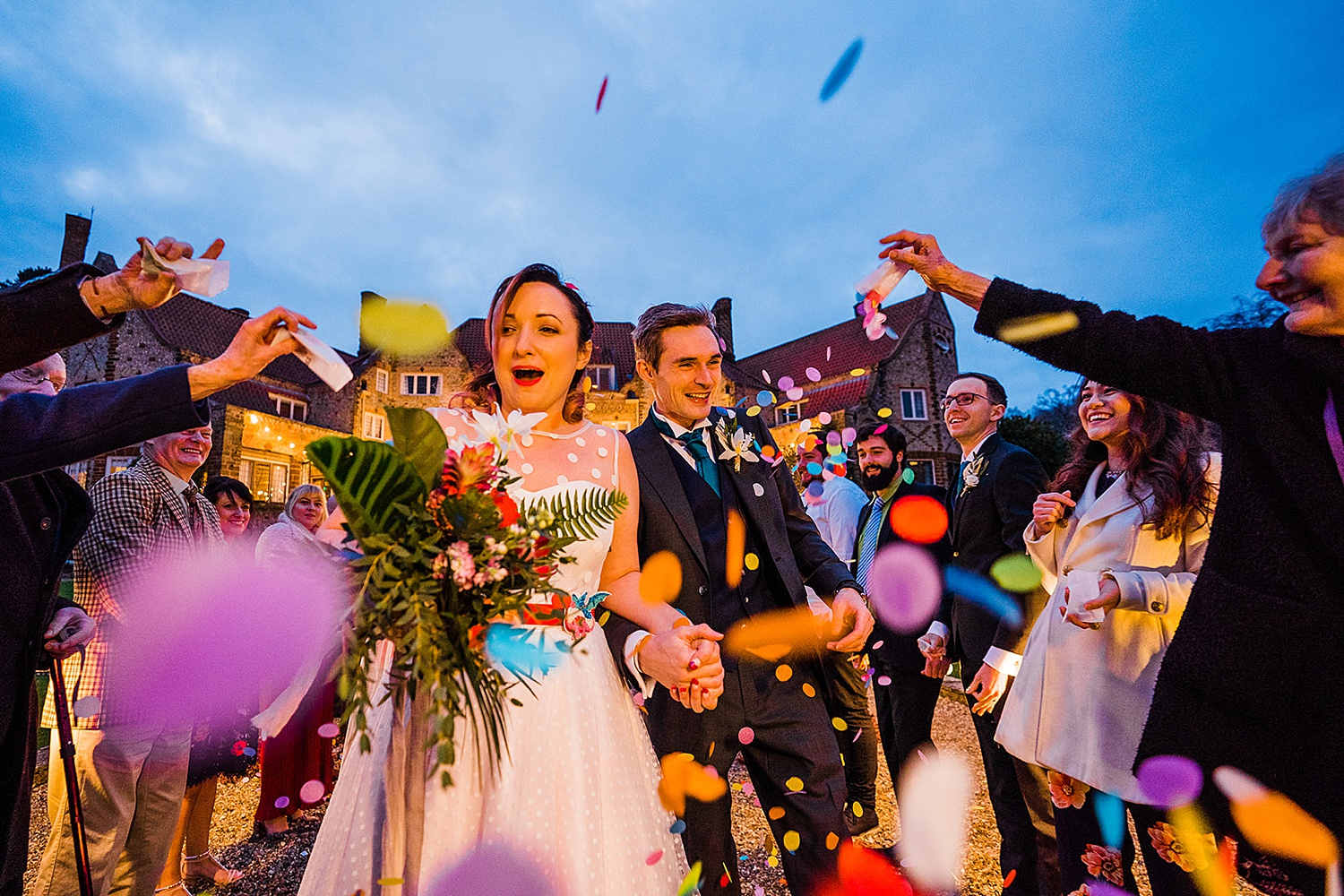 Bride and groom being showered by colourful confetti Voewood wedding