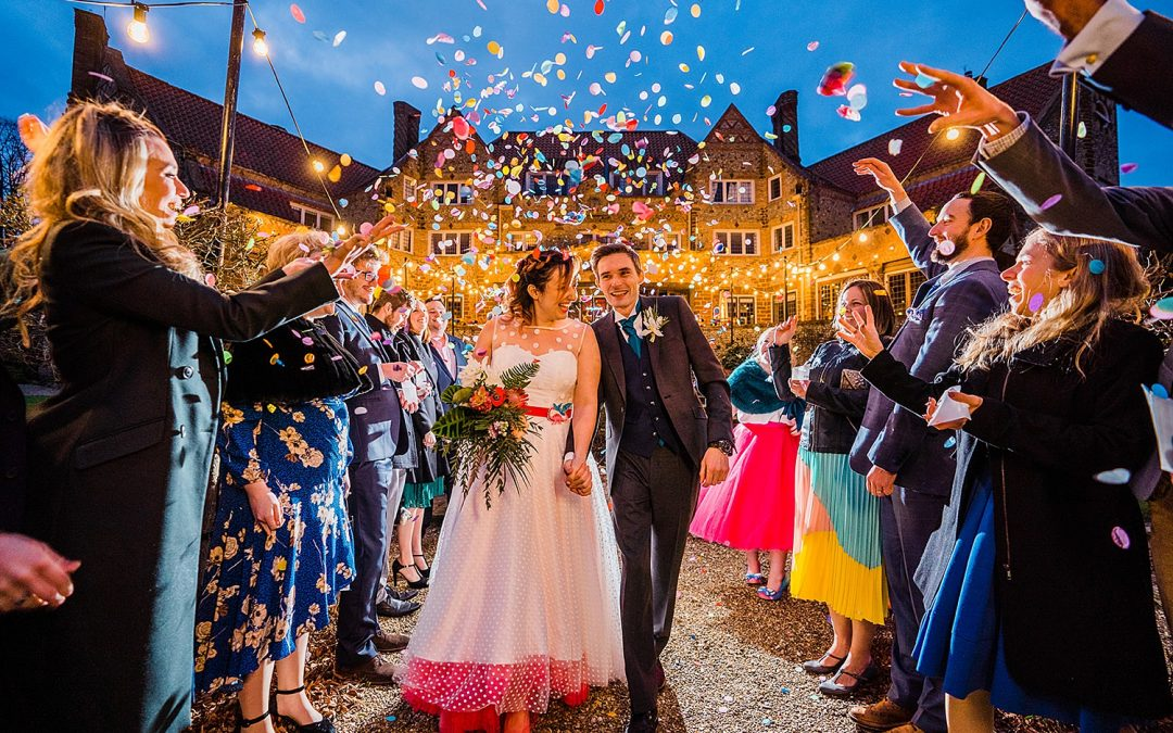 Bride and groom walk through rainbow coloured confetti tunnel at dusk during winter wedding at Voewood House. Image by Parrot and Pineapple