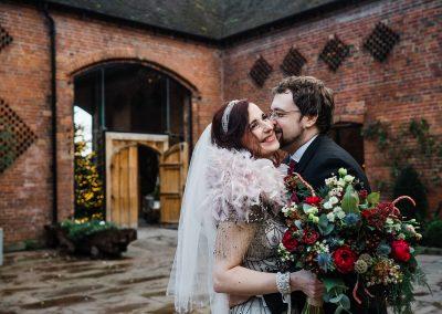 Groom kissing bride on cheek Shustoke Barn wedding