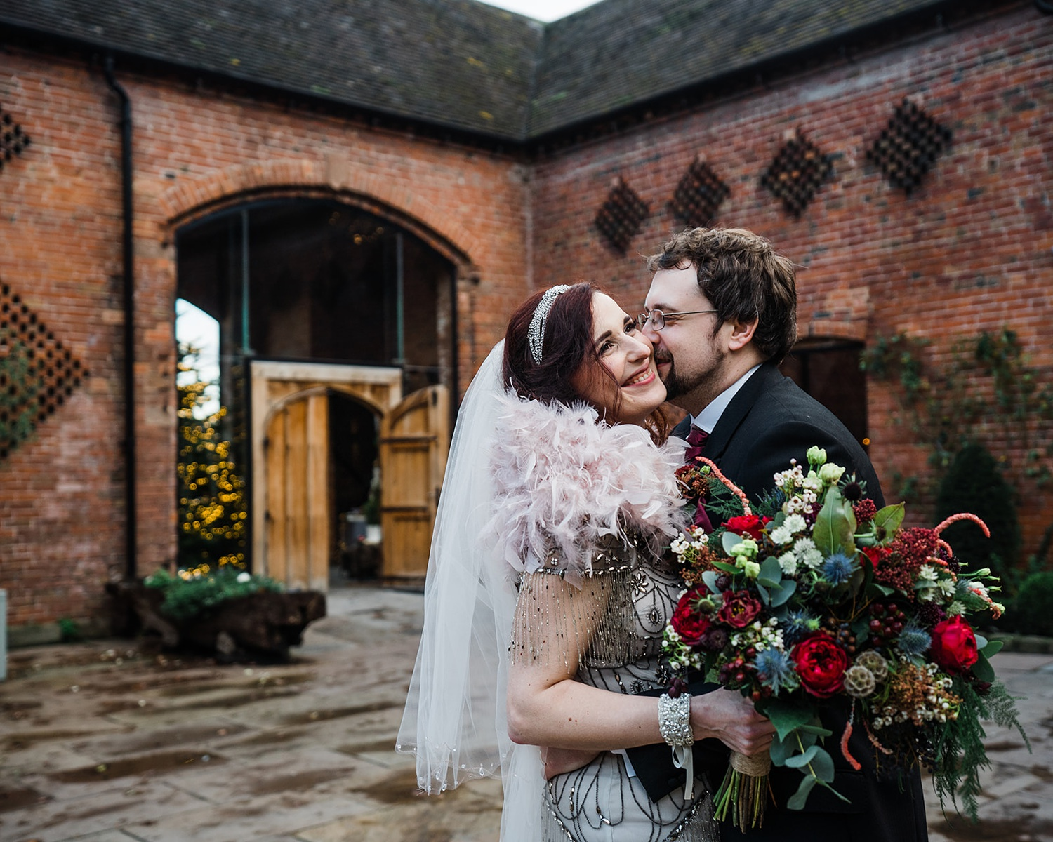 Groom kissing bride on cheek Shustoke Barn wedding