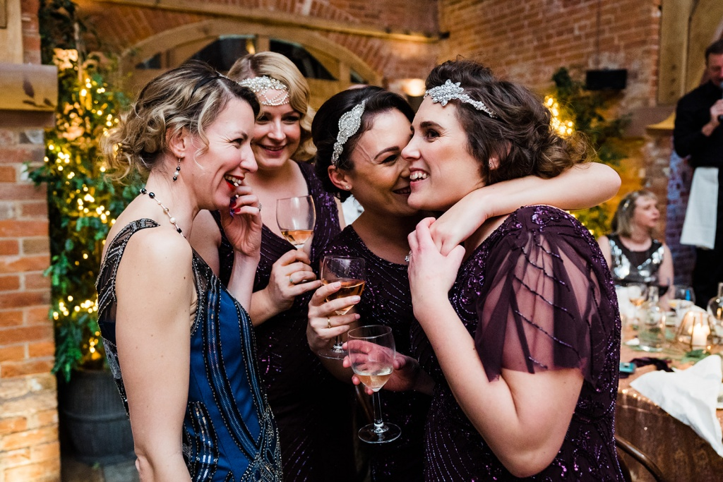 bridesmaids huddle together arms round each other at a glitzy christmas wedding at shustoke farm barn. Image by documentary wedding photographer parrot and pineapple.