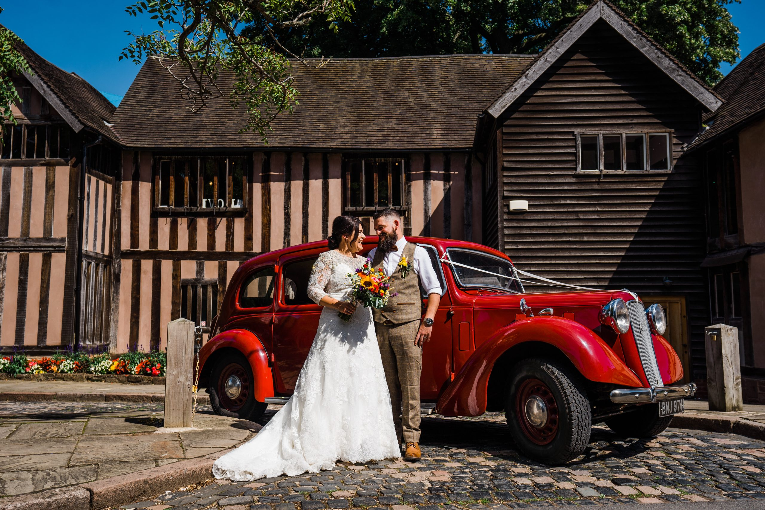 Bride and groom in front of red car Kingstanding-Farm-Wedding