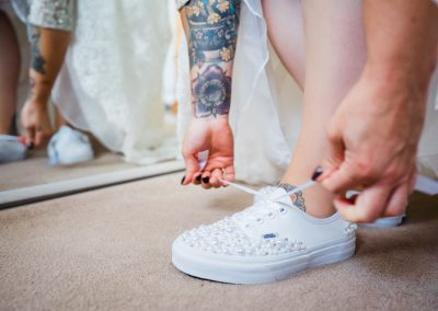 Bride putting on white bridal trainers