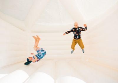 Two people bouncing on white bouncy castle