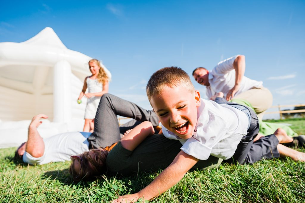 three children and a man fall on to the grass from a bouncy castle at a festival wedding at kingstanding farm. image by parrot and pineapple.