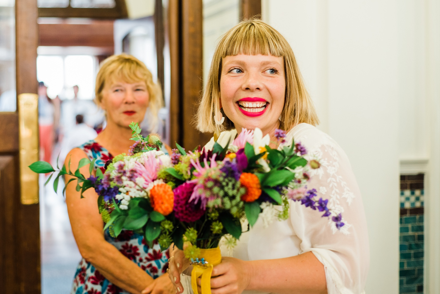 Trendy bride with pink lipstick smiling at Peckham Employment Academy Wedding